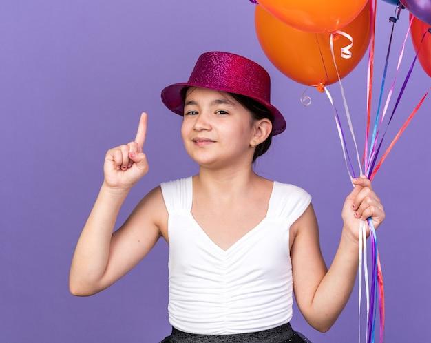 Довольная молодая кавказская девушка с фиолетовой шляпой держит гелиевые шары и указывает вверх изолирована на фиолетовой стене с копией пространства