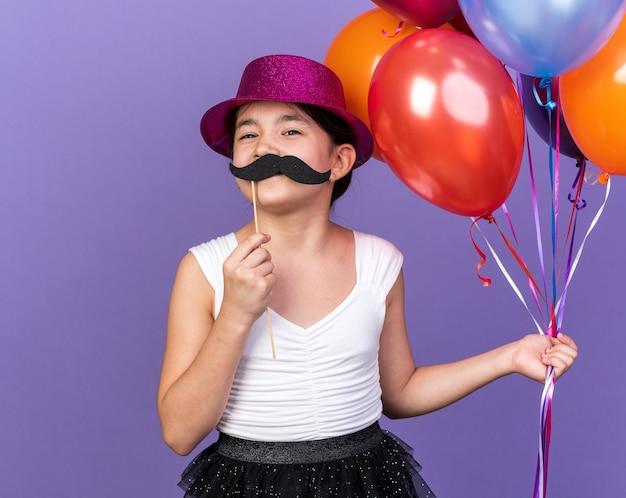 Contenta giovane ragazza caucasica con cappello da festa viola che tiene palloncini di elio e baffi finti su bastone isolato su parete viola con spazio di copia