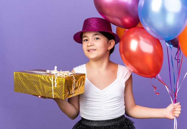 Pleased young caucasian girl with violet party hat holding helium balloons and gift box isolated on purple wall with copy space
