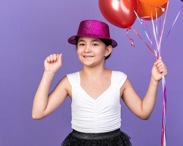 Contenta giovane ragazza caucasica con cappello da festa viola che tiene in mano palloncini di elio e tiene il pugno alzato isolato sul muro viola con spazio di copia
