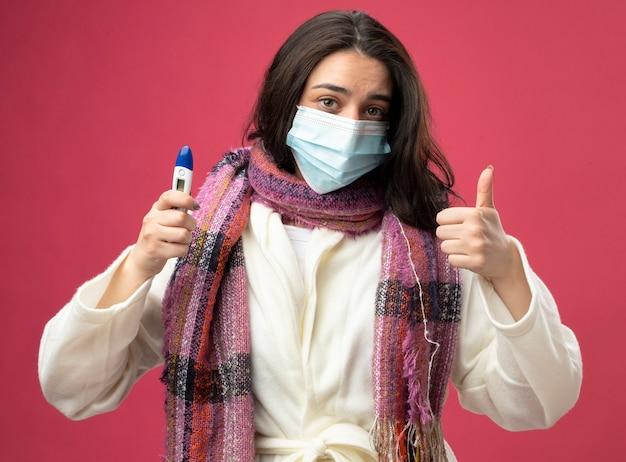 真っ赤な壁に隔離された親指を示す温度計を保持しているマスクとローブとスカーフを身に着けている若い白人の病気の女の子を喜ばせる