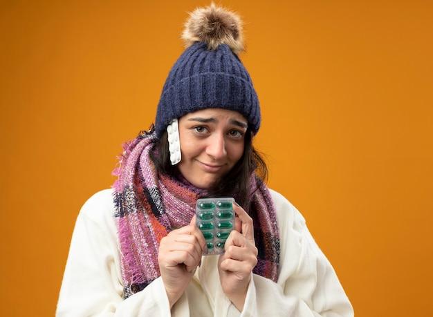コピースペースのあるオレンジ色の壁に隔離された帽子の下にタブレットのパックとカプセルのパックを保持しているローブの冬の帽子とスカーフを身に着けている若い白人の病気の女の子を喜ばせる