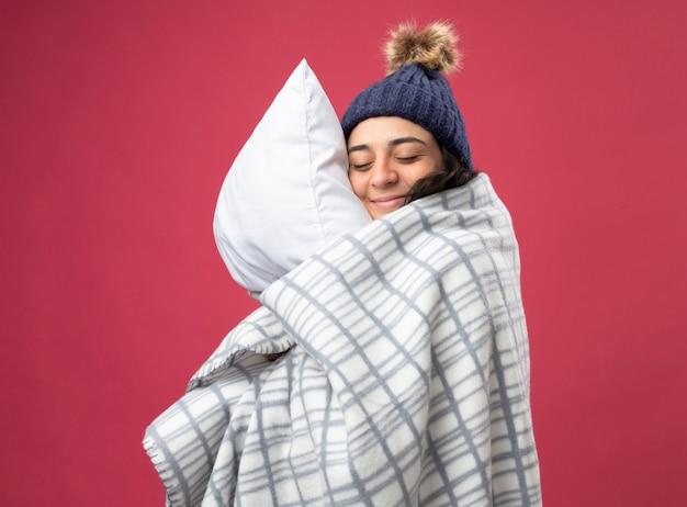 Довольная молодая кавказская больная девушка в зимней шапке и шарфе, завернутом в плед, стоит в профиль и обнимает подушку с закрытыми глазами, изолированными на малиновом фоне с копией пространства