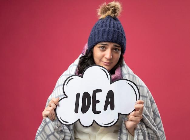 Felice giovane indoeuropeo ragazza malata che indossa robe inverno cappello e sciarpa avvolto in plaid azienda bolla idea guardando la telecamera isolata su sfondo cremisi