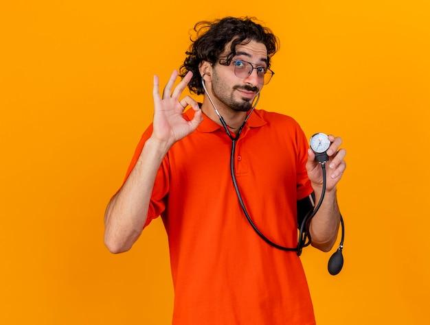 Довольный молодой кавказский больной в очках и стетоскопе, держащий сфигмоманометр, делает хорошо, знак изолирован на оранжевой стене с копией пространства