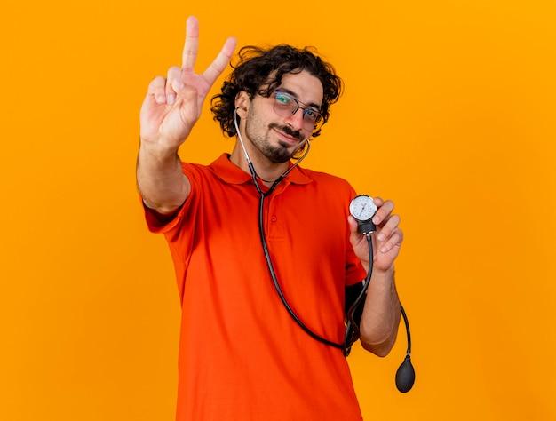 Довольный молодой кавказский больной в очках и стетоскопе держит сфигмоманометр, делающий знак мира, изолированный на оранжевой стене с копией пространства