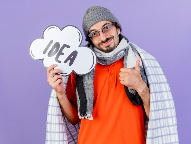 Pleased young caucasian ill man wearing glasses winter hat and scarf wrapped in plaid holding idea bubble looking at camera showing thumb up isolated on purple background