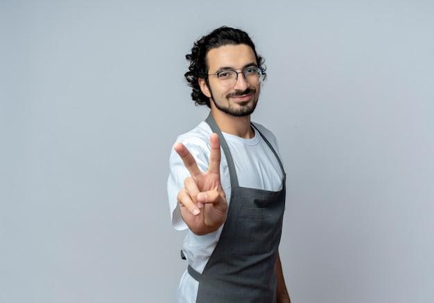 Довольный молодой кавказский мужчина-парикмахер в очках и волнистой повязке для волос в униформе делает знак мира на белом фоне с копией пространства