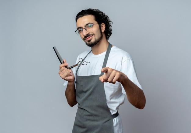 Довольный молодой кавказский мужчина-парикмахер в очках и волнистой повязке для волос в униформе, держа расческу и ножницы, указывая на камеру, изолированную на белом фоне с копией пространства