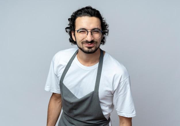 Довольный молодой кавказский мужчина-парикмахер в очках и волнистой повязке для волос в униформе смотрит в камеру, изолированную на белом фоне с копией пространства