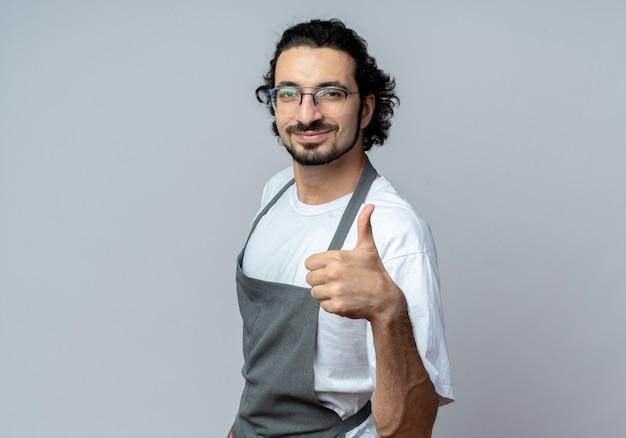 Довольный молодой кавказский мужчина-парикмахер в очках и волнистой повязке для волос в униформе, стоя в профиле, показывая большой палец вверх изолирован на белом фоне с копией пространства