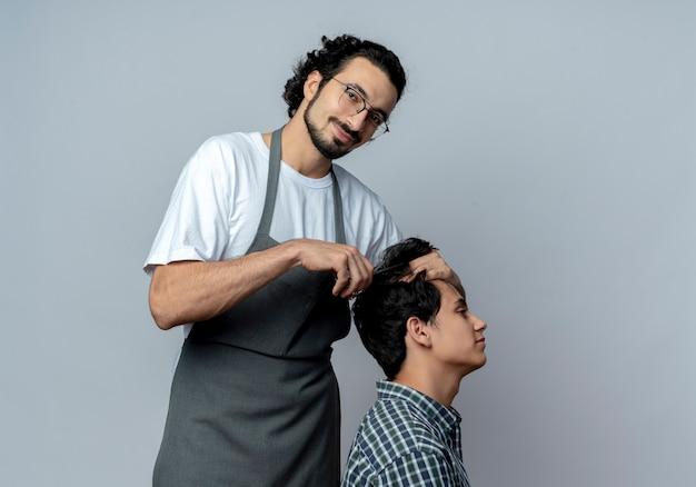 Lieto giovane maschio caucasico barbiere con gli occhiali e fascia per capelli ondulati in uniforme facendo taglio di capelli per il suo giovane cliente