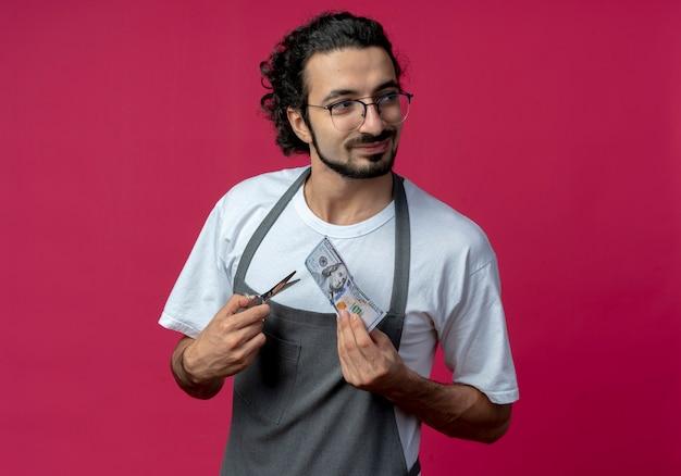 Lieto giovane maschio caucasico barbiere con gli occhiali e fascia per capelli ondulati in uniforme che tiene soldi e forbici guardando lato isolato su sfondo cremisi con spazio di copia