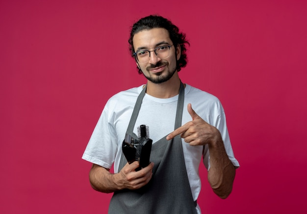 Pleased young caucasian male barber wearing glasses and wavy hair band in uniform holding and pointing at hair clippers, comb, spray bottle isolated on crimson background with copy space
