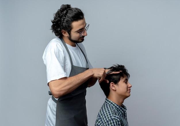 Lieto giovane maschio caucasico barbiere con gli occhiali e fascia per capelli ondulati in uniforme in piedi in vista di profilo facendo taglio di capelli per il suo giovane cliente