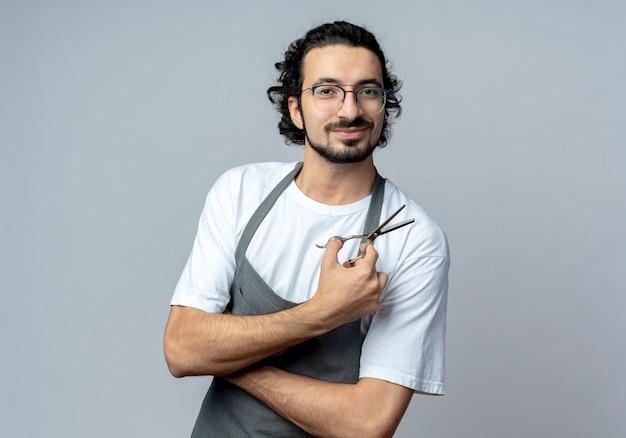 Lieto giovane maschio caucasico barbiere con gli occhiali e fascia per capelli ondulati in uniforme in piedi con la postura chiusa e tenendo le forbici isolate su sfondo bianco con spazio di copia