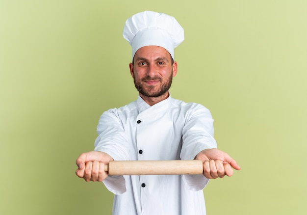 Pleased young caucasian male cook in chef uniform and cap looking at camera stretching out rolling pin towards camera isolated on olive green wall