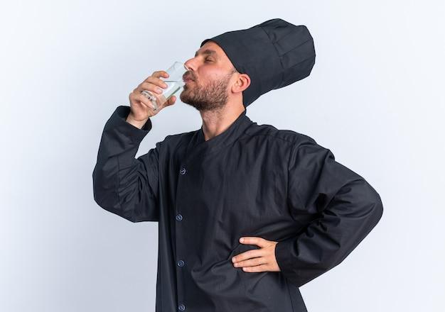 シェフの制服を着た若い白人男性料理人を喜ばせ、白い壁に隔離された目を閉じて腰に手を置いて水を飲みながら縦断ビューで立っているキャップ