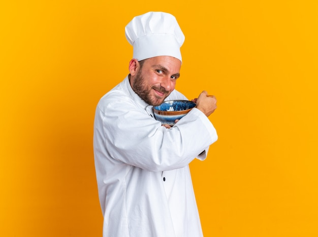 Довольный молодой кавказский мужчина-повар в униформе шеф-повара и кепке, стоящий в профиле, смотрит в камеру, держащую миску и ложку, обнимающую миску, изолированную на оранжевой стене с копией пространства