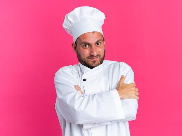 Довольный молодой кавказский повар в униформе шеф-повара и кепке, стоя в закрытой позе, глядя в камеру, изолированную на розовой стене