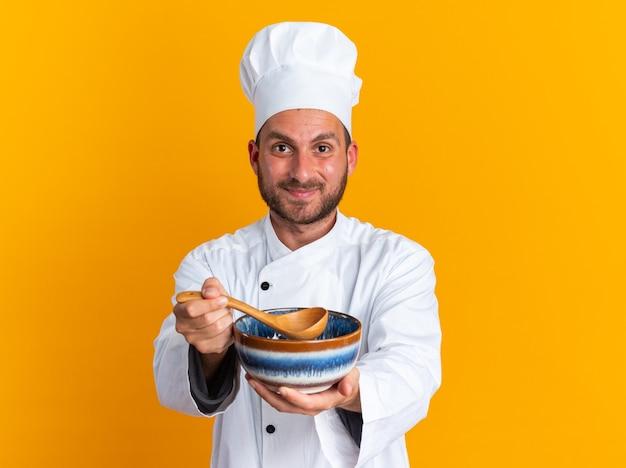 Довольный молодой кавказский повар в униформе шеф-повара и кепке протягивает миску и ложку к камере