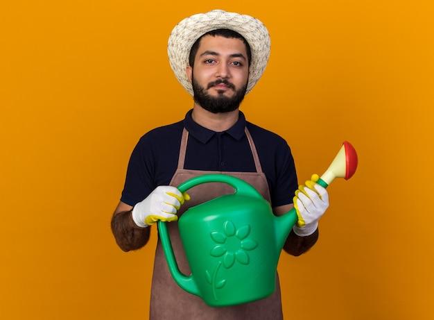 원예 모자와 물을 들고 장갑을 끼고 기쁘게 젊은 백인 남성 정원사 복사 공간이 오렌지 벽에 격리 수 있습니다