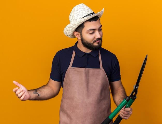 コピースペースでオレンジ色の壁に分離されたガーデニングはさみを保持し、見てガーデニング帽子をかぶっている若い白人男性の庭師を喜ばせる