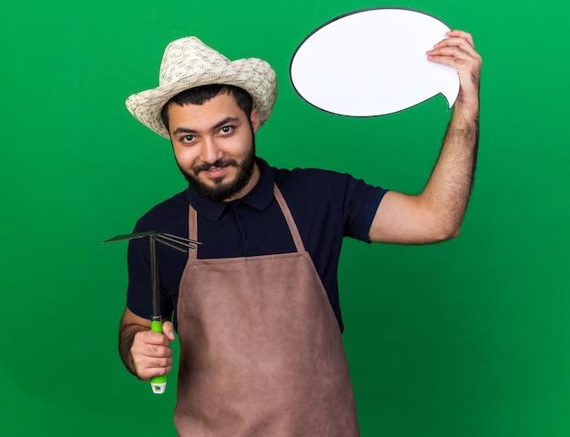 Piacere giovane maschio caucasico giardiniere indossando giardinaggio hat holding hoe rastrello e discorso palloncino isolato sulla parete verde con copia space