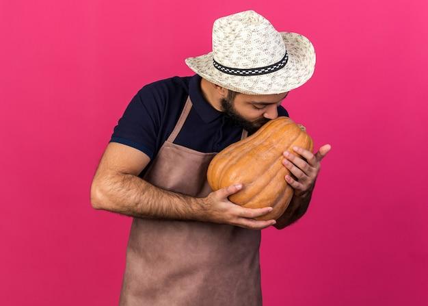 Felice giovane maschio caucasico giardiniere indossando giardinaggio hat holding e baciare la zucca isolata sulla parete rosa con spazio di copia with