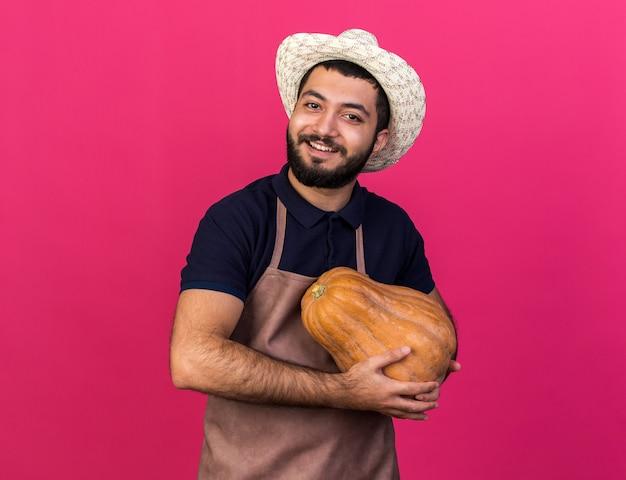 Soddisfatto giovane maschio caucasico giardiniere che indossa cappello da giardinaggio tenendo la zucca isolata sulla parete rosa con spazio di copia