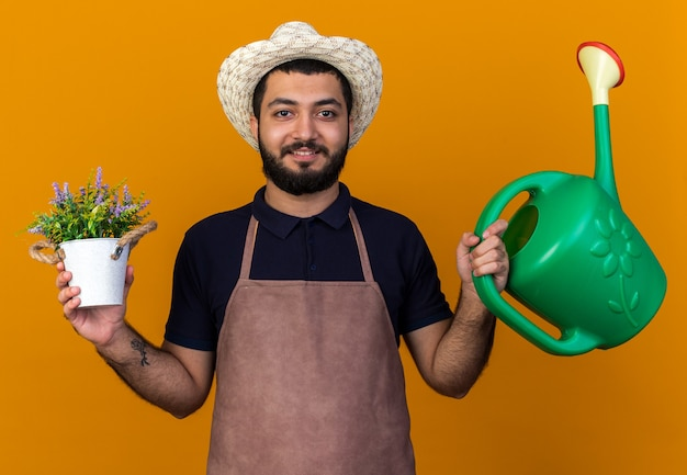 Pleased young caucasian male gardener wearing gardening hat holding watering can and flowerpot isolated on orange wall with copy space