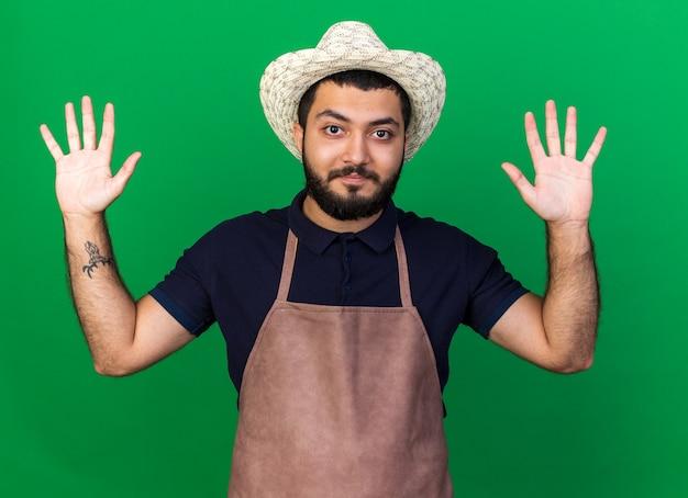 Довольный молодой кавказский садовник в садовой шляпе, стоящий с поднятыми руками, изолированными на зеленой стене с копией пространства
