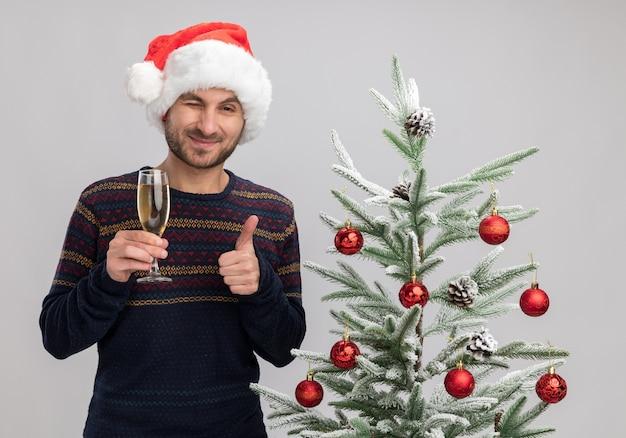 카메라 윙크와 엄지 손가락을 보여주는 샴페인 잔을 들고 크리스마스 트리 근처 서 크리스마스 모자를 쓰고 기쁘게 젊은 백인 남자는 흰색 배경에 고립