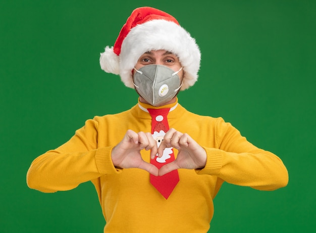 Pleased young caucasian man wearing christmas hat and tie with protective mask looking at camera doing heart sign isolated on green background