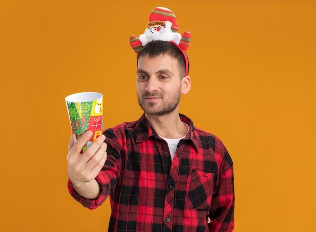 Felice giovane uomo caucasico indossando la fascia di babbo natale allungando la tazza di plastica di natale verso la telecamera guardando la tazza isolata su sfondo arancione con copia spazio