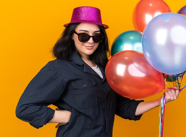 オレンジ色の壁で隔離された腰に手を保持している風船を保持しているパーティー帽子とサングラスを身に着けている若い白人のパーティーの女の子を喜ばせる