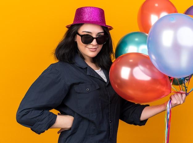 Felice giovane ragazza caucasica che indossa cappello da festa e occhiali da sole che tengono palloncini tenendo la mano sulla vita isolata sulla parete arancione