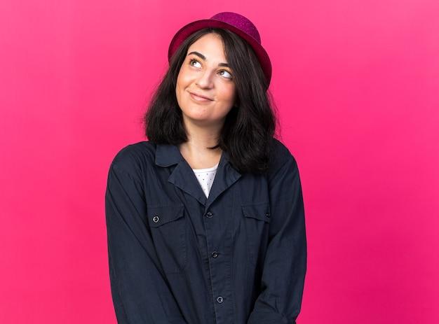 Felice giovane festa caucasica donna che indossa cappello da festa guardando in alto isolato sulla parete rosa