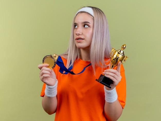Lieta giovane ragazza sportiva caucasica con bretelle che indossa fascia e braccialetti tiene la medaglia d'oro e la coppa del vincitore guardando a lato