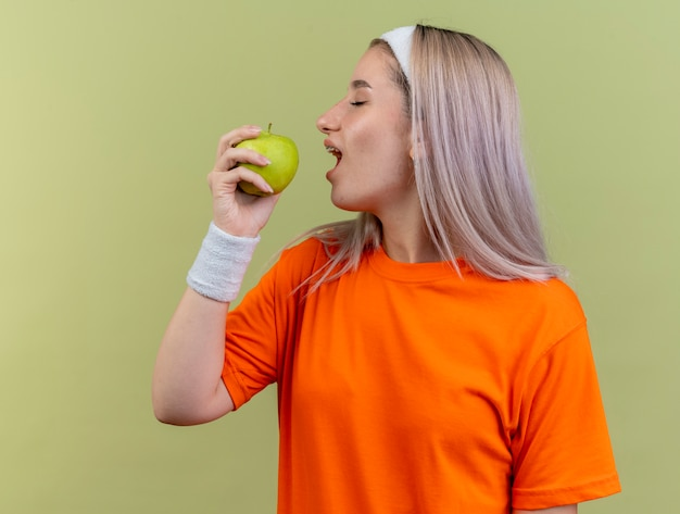 Felice giovane ragazza sportiva caucasica con bretelle che indossa fascia e braccialetti finge di mordere la mela