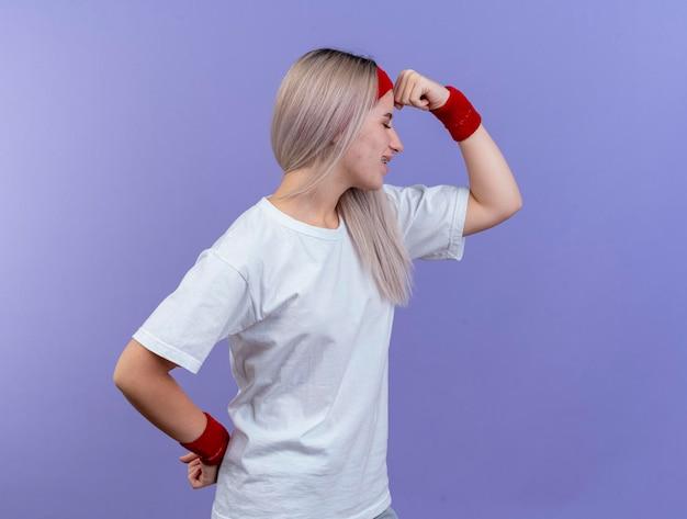 Felice giovane ragazza sportiva caucasica con le parentesi graffe che indossa la fascia