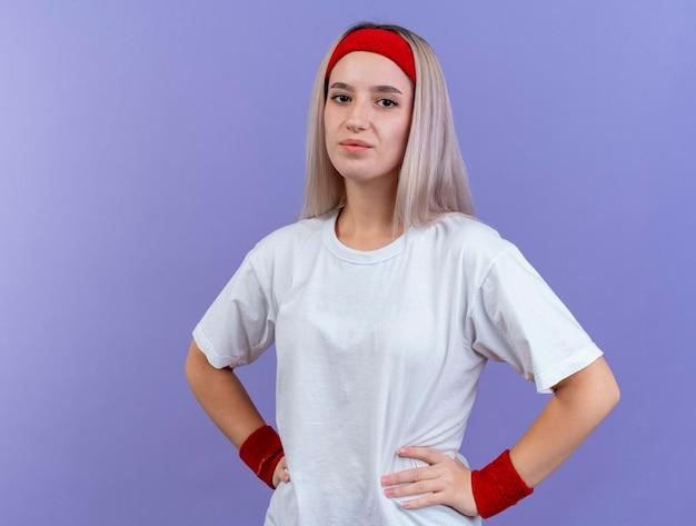 머리띠를 착용 중괄호와 기쁘게 젊은 백인 스포티 한 소녀