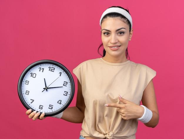 Lieta giovane donna sportiva caucasica che indossa fascia e braccialetti che tengono e puntano all'orologio guardando la parte anteriore isolata sulla parete rosa