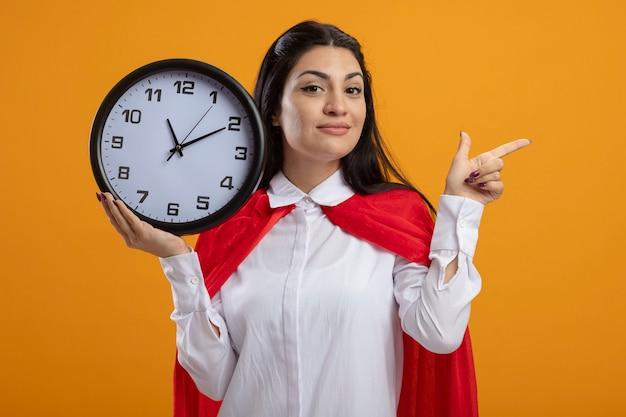 Довольный молодой кавказский супергерой девушка держит часы, глядя в камеру, указывая на сторону, изолированную на оранжевом фоне