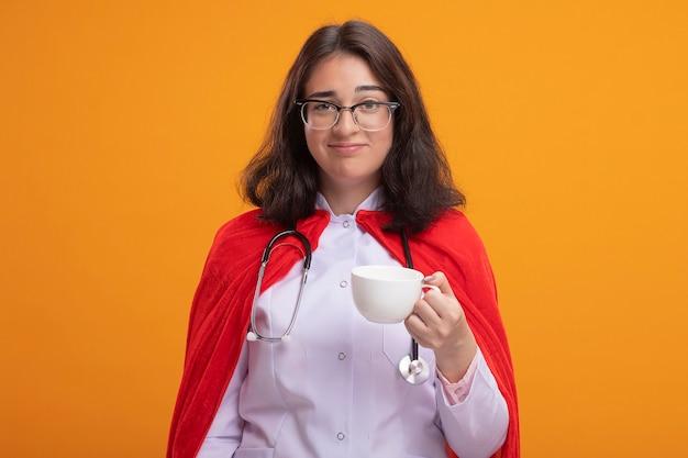 Lieta giovane ragazza caucasica del supereroe che indossa l'uniforme del medico e uno stetoscopio con gli occhiali che tengono una tazza di tè