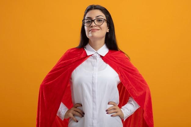 オレンジ色の背景で隔離のカメラを見て腰に手を置いて眼鏡をかけている若い白人のスーパーヒーローの女の子を喜ばせる