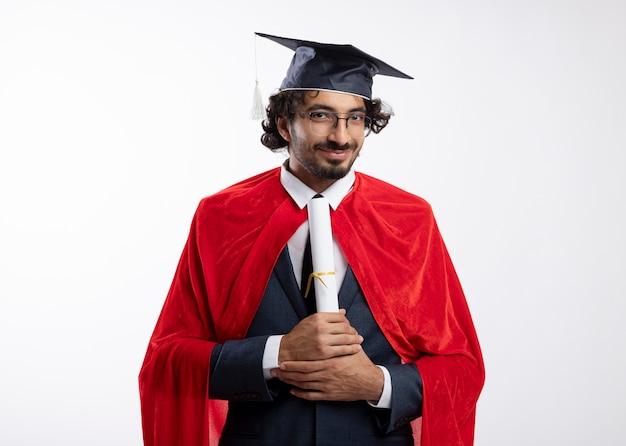Felice giovane supereroe caucasico uomo in occhiali ottici che indossa tuta con mantello rosso e cappello di laurea tiene diploma isolato su sfondo bianco con spazio di copia
