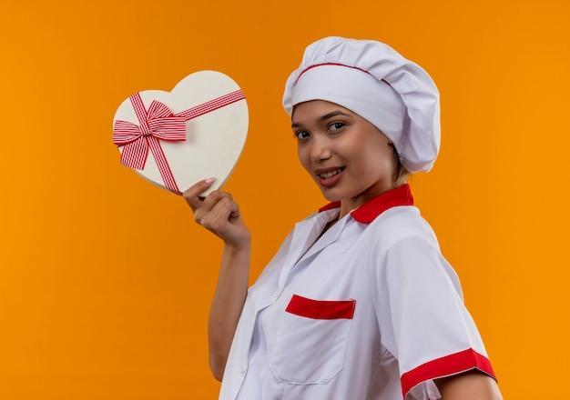 Lieta giovane cuoco femmina che indossa uniforme da chef tenendo la scatola a forma di cuore sulla parete arancione isolata
