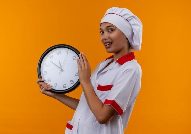 コピースペースのある孤立したオレンジ色の壁に壁時計を保持しているシェフの制服を着ている若い料理人の女性を喜ばせる
