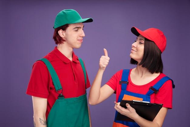 Felice giovane coppia in uniforme da operaio edile e berretto che si guarda l'un l'altro ragazza con matita e appunti che mostra pollice in su isolato su parete viola